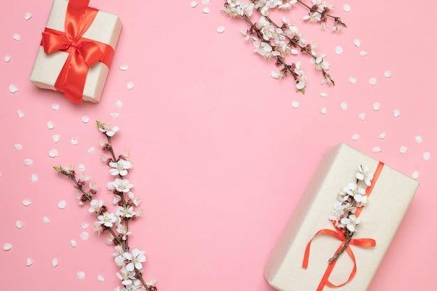 Überraschen sie geschenkbox mit einem roten bogen auf einem rosa backgroun