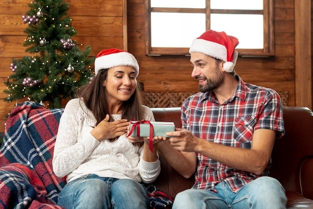 Überraschende frau des ehemanns des mittleren schusses mit geschenk