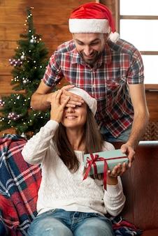 Überraschende frau des mittleren schussmannes mit geschenk