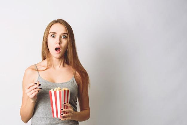 Überraschende frau, die popcorn isst. mädchen, das große gestreifte schachtel mit kinoteil popcorn hält. beeindruckend
