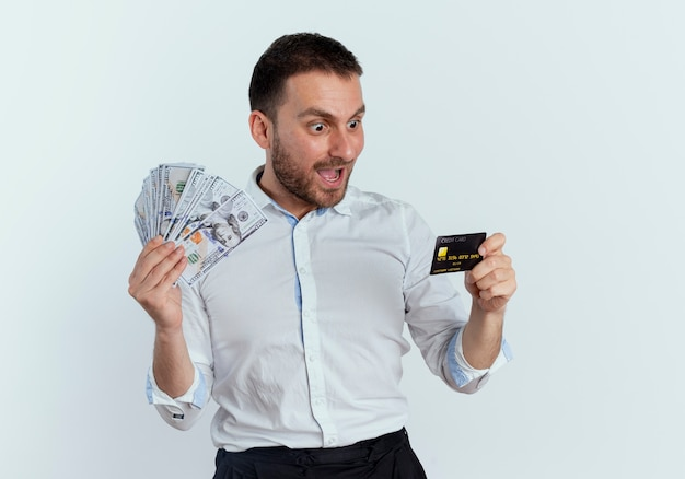 Überraschender gutaussehender mann hält geld und betrachtet kreditkarte lokalisiert auf weißer wand