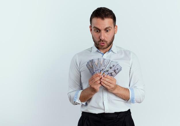 Überraschender gutaussehender mann hält und betrachtet geld isoliert auf weißer wand