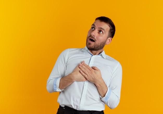 Überraschender gutaussehender mann legt hände auf brust, die isoliert auf orange wand nach oben schauen