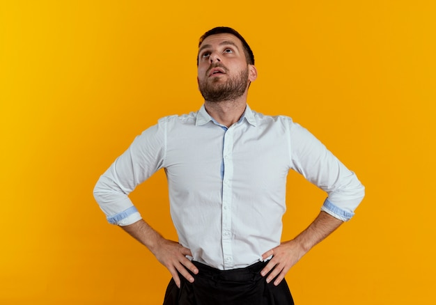 Überraschender gutaussehender mann legt hände auf taille und schaut isoliert auf orange wand nach oben