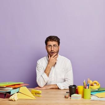 Überraschender hübscher angestellter, der am schreibtisch sitzt