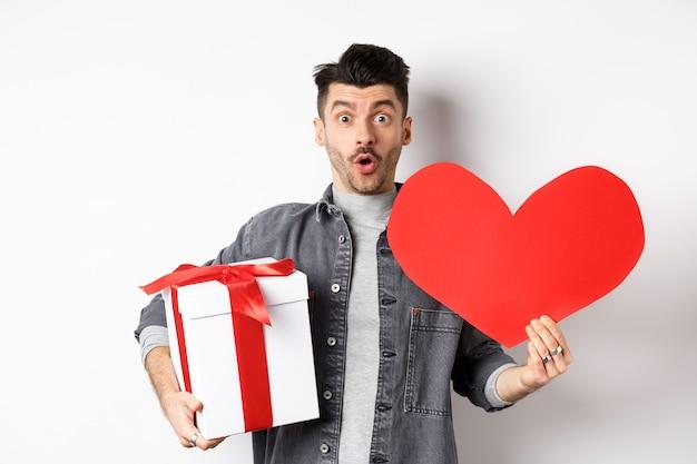 Überraschender hübscher kerl, der romantische rote herzkarte und geschenkbox hält, sagen wow und betrachten kamera erstaunt, feiert liebhaberurlaub, weiß. valentinstag konzept.