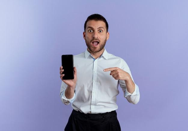 Überraschender hübscher mann hält und zeigt auf telefon lokalisiert auf lila wand