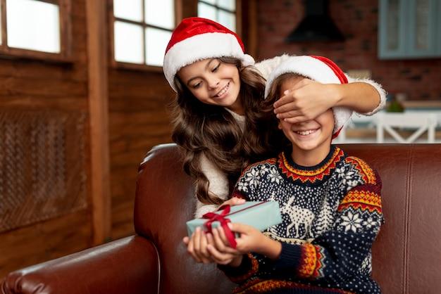 Überraschender junge des mittleren schussmädchens mit geschenk