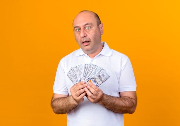 Überraschender lässiger reifer mann, der bargeld lokalisiert auf gelber wand hält
