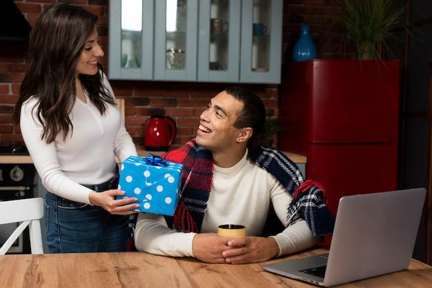 Überraschender mann der schönen frau mit einem geschenk
