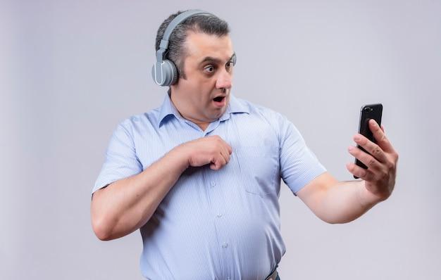 Überraschender mann mittleren alters im blau gestreiften hemd, das kopfhörer trägt, die sein smartphone auf einem weißen hintergrund betrachten