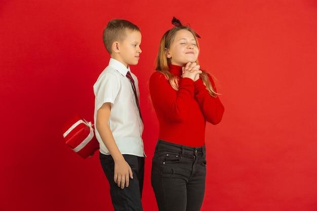 Überraschender moment. valentinstagfeier, glückliche, niedliche kaukasische kinder lokalisiert auf rotem studiohintergrund. konzept der menschlichen gefühle, gesichtsausdruck, liebe, beziehungen, romantische feiertage.