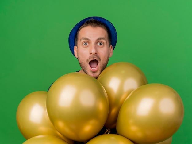 Überraschender schöner kaukasischer mann, der blauen parteihut trägt, steht mit heliumballons, die kamera lokalisiert auf grünem hintergrund mit kopienraum betrachten