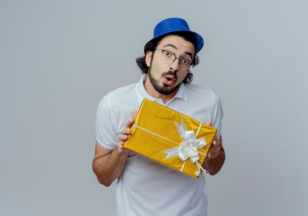 Überraschender schöner mann, der brille und blauen hut hält geschenkbox lokalisiert auf weiß trägt