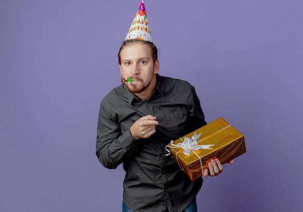 Überraschender schöner mann in der geburtstagskappe hält und zeigt auf geschenkbox, die pfeife lokalisiert auf lila wand bläst