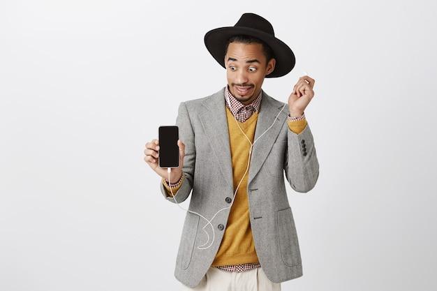 Überrascht afroamerikaner kerl abnehmen kopfhörer überfallen und ungeschickt, blick auf smartphone-bildschirm, zeigt mobile anzeige