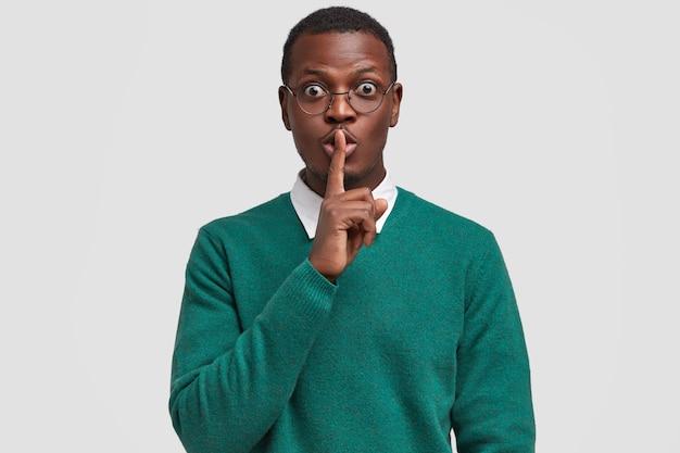 Überrascht attraktiver schwarzer mann hält zeigefinger über mund, zeigt schweigezeichen, bittet, sein geheimnis nicht zu verraten