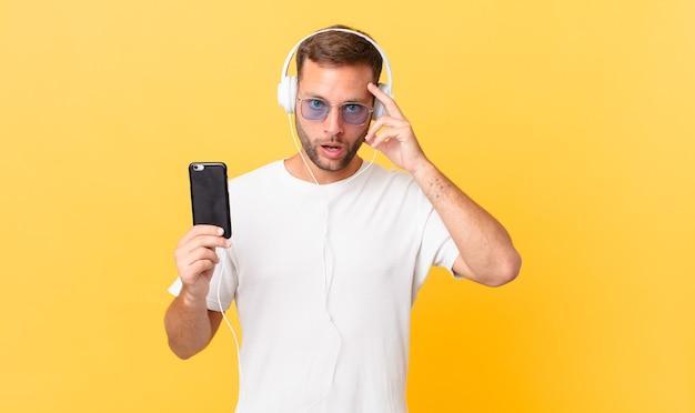Überrascht aussehen, einen neuen gedanken, eine neue idee oder ein neues konzept verwirklichen, musik mit kopfhörern und einem smartphone hören
