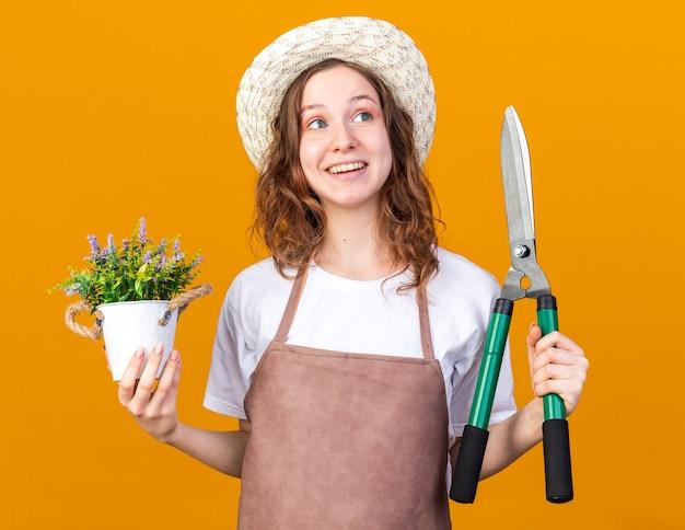 Überrascht aussehende junge gärtnerin mit gartenhut, die blume im blumentopf mit gartenschere hält
