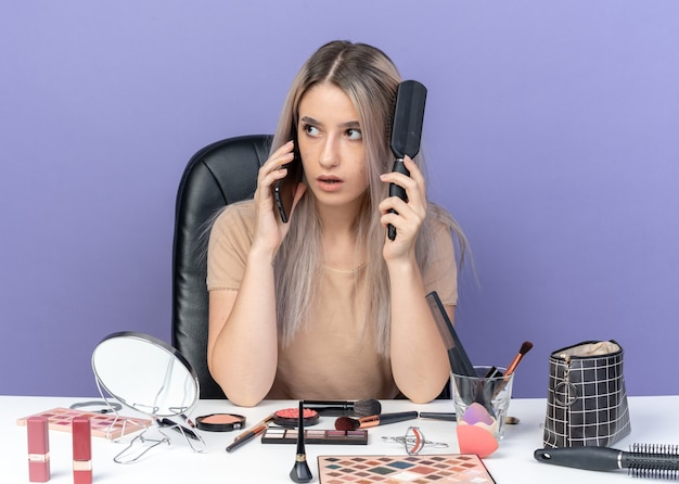 Überrascht aussehendes junges schönes mädchen sitzt am tisch mit make-up-tools spricht am telefon und kämmt haare einzeln auf blauem hintergrund