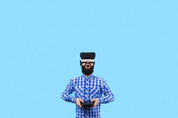 Überrascht bärtiger mann in vr (virtual-reality-brille) mit fernbedienung in der hand steuert die drohne