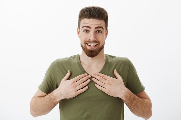 Überrascht dankbar und erstaunt fröhlicher junger bärtiger mann im olivgrünen t-shirt, der die augenbrauen hochzieht, erstaunt und aufgeregt lächelnd, mit einem unerwarteten geschenk betäubt, das handflächen auf der brust hält