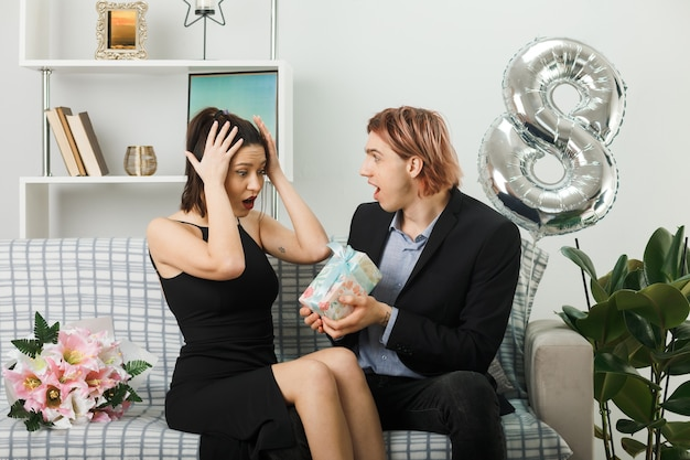 Überrascht, das junge paar am glücklichen frauentag anzuschauen, das das gegenwärtige mädchen hält, schnappte sich den kopf, der auf dem sofa im wohnzimmer sitzt