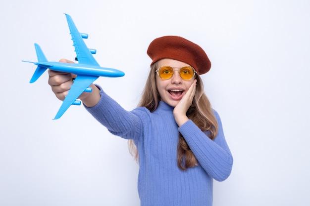 Überrascht, die hand auf die wange legen schönes kleines mädchen mit brille mit hut, das spielzeugflugzeug heraushält