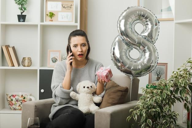 Überrascht, ein schönes mädchen an einem glücklichen frauentag mit geschenk zu suchen, spricht am telefon, das auf einem sessel im wohnzimmer sitzt