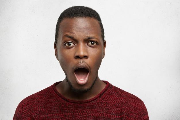 Überrascht emotionaler junger schwarzer mann, der faszinierten blick verblüfft, mund weit öffnet und augenbrauen hochzieht, schockiert von hohen verkaufspreisen, isoliert stehend