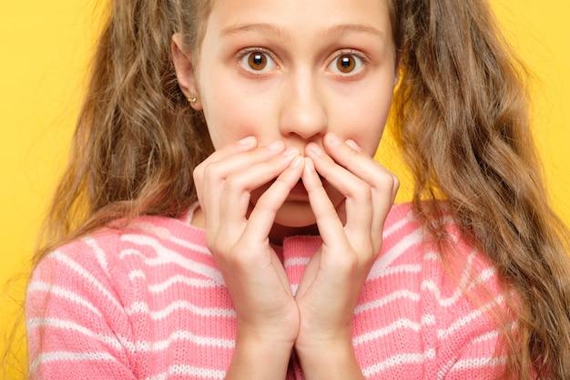 Überrascht erstaunt erstauntes mädchen, das ihren mund mit den händen bedeckt. emotionale reaktion