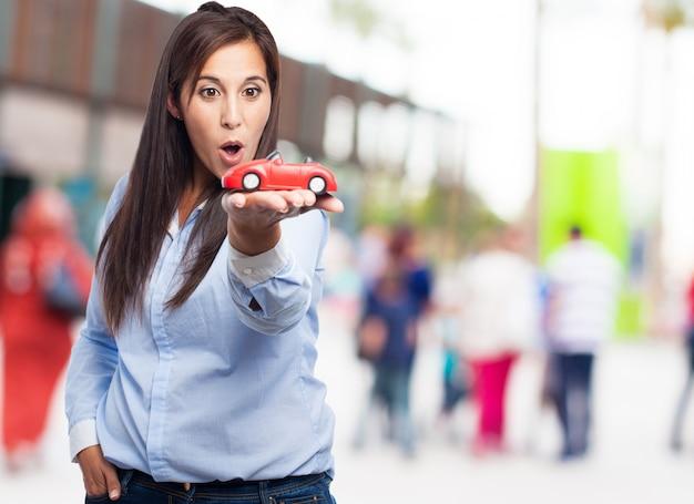 Überrascht frau mit einem roten auto halten