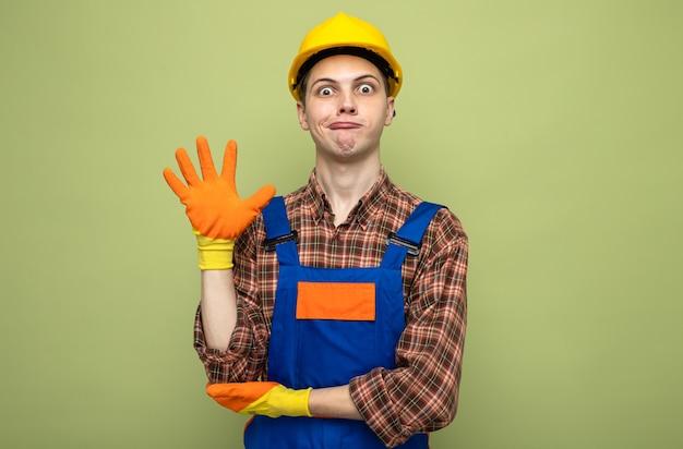 Überrascht, fünf junge männliche baumeister in uniform mit handschuhen zu zeigen