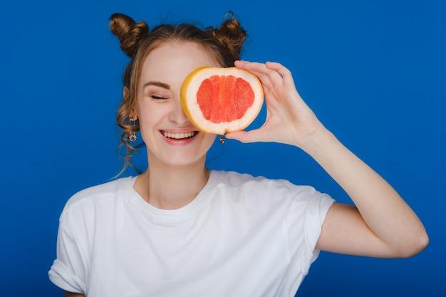 Überrascht hält das lachende mädchen die grapefruit wie ohren.