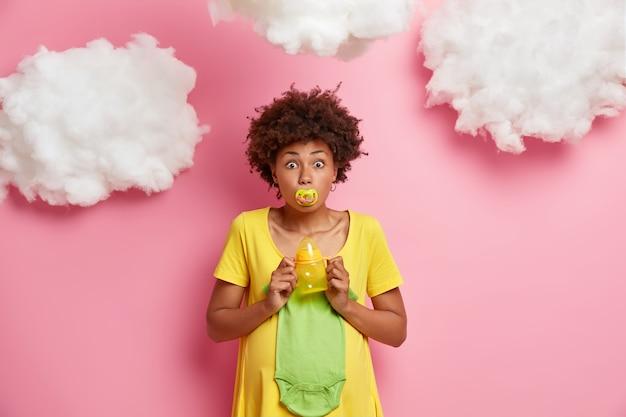 Überrascht hält schwangere zukünftige mutter brustwarzen in mund posen mit babykleidung und notwendigkeiten macht sich bereit für entbindungsklinik posen drinnen