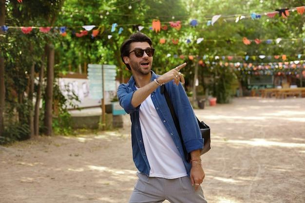 Überrascht hübscher junger mann mit bart, der in freizeitkleidung und sonnenbrille durch den grünen park geht, etwas interessantes bemerkt und dort mit dem zeigefinger zeigt