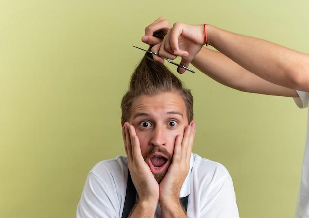 Überrascht junger hübscher friseur, der hände auf gesicht setzt, hat angst, alle seine haare abgeschnitten auf olivgrüner wand abgeschnitten zu bekommen