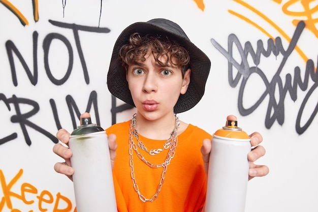 Überrascht kreeative teenager stört straßenmauern hält zwei aerosolsprays macht graffiti hat sich ausdruck gefragt