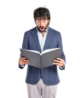 Überrascht mann liest ein buch über weißem hintergrund