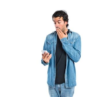 Überrascht mann reden mit handy über weißem hintergrund