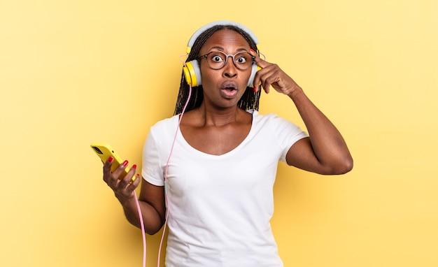 Überrascht, mit offenem mund, schockiert aussehen, einen neuen gedanken, eine neue idee oder ein neues konzept verwirklichen und musik hören