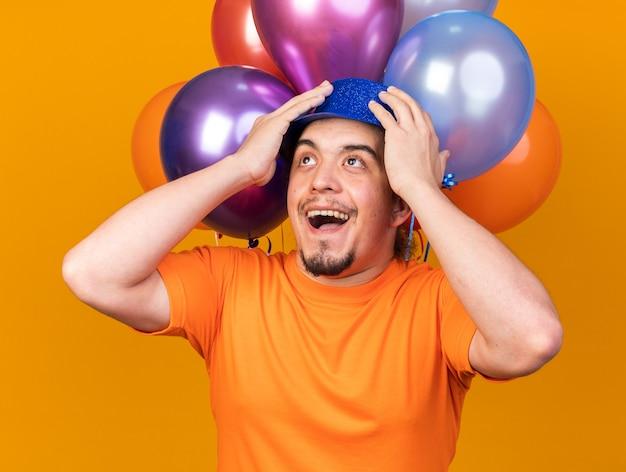 Überrascht nachschlagender junger mann mit partyhut, der vor luftballons stand, packte den kopf