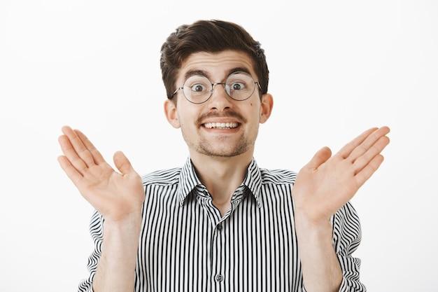 Überrascht nerdiger freund mit schnurrbart und bart in brille, handflächen heben und breit lächeln, augenbrauen vor überraschung und erstaunen heben, handflächen umklammern, zufrieden und zufrieden mit dem ergebnis