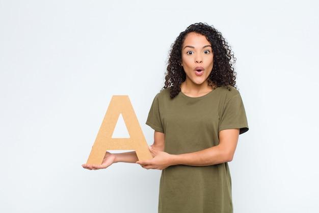 Überrascht, schockiert, erstaunt, den buchstaben a des alphabets haltend, um ein wort oder einen satz zu bilden.