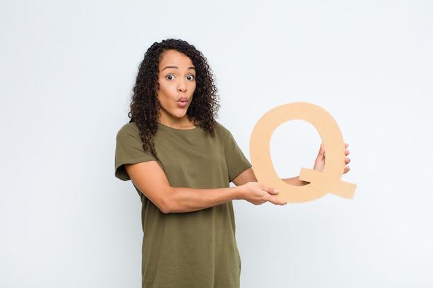 Überrascht, schockiert, erstaunt, den buchstaben q des alphabets haltend, um ein wort oder einen satz zu bilden.