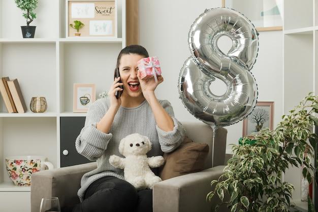 Überrascht, schönes mädchen an einem glücklichen frauentag mit geschenk zu suchen, spricht am telefon, das auf einem sessel im wohnzimmer sitzt