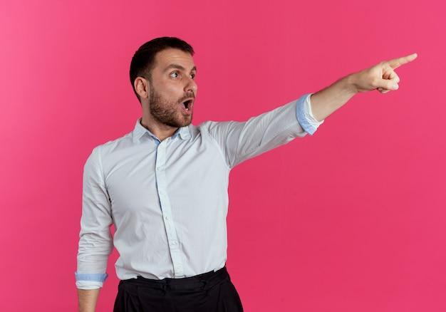 Überrascht sieht gutaussehender mann und zeigt zur seite isoliert auf rosa wand