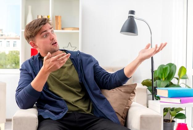 Überrascht sitzt junger blonder gutaussehender mann auf sessel und schaut und zeigt mit zwei händen im wohnzimmer zur seite