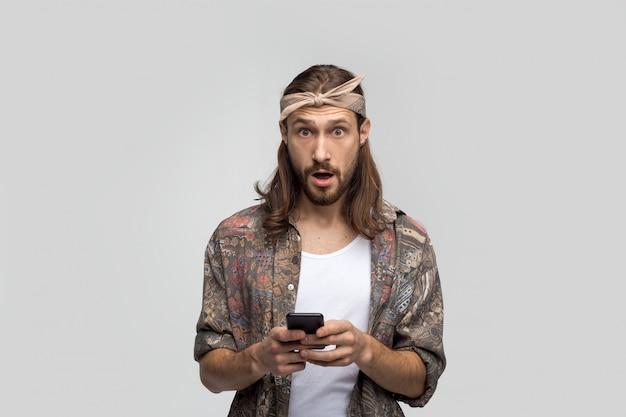 Überrascht und schockiert junger bärtiger hipster-typ, der die kamera betrachtet, ein smartphone in seinen händen hält, nachrichten lernt, den benutzer des 5g-internets und der modernen technologie