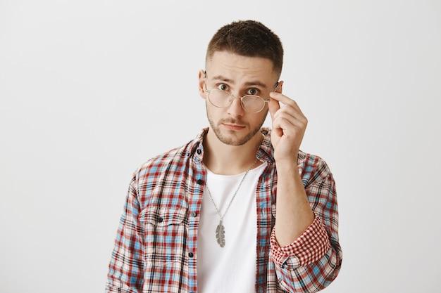 Überrascht und verwirrt junger mann mit brille posiert